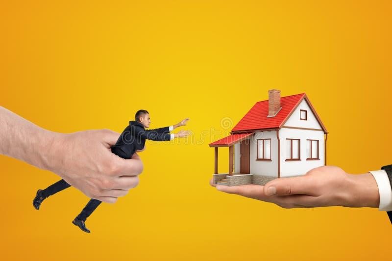Den stora handen på den vänstra hållande småföretagaren som ut når med hans båda händer för det lilla huset som står på, gömma i  royaltyfri foto