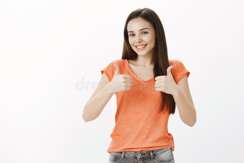 Den stora idén, som den och älskar den Studiostående av den lyckliga snygga bekymmerslösa kvinnan i orange blus som visar tummar royaltyfri bild