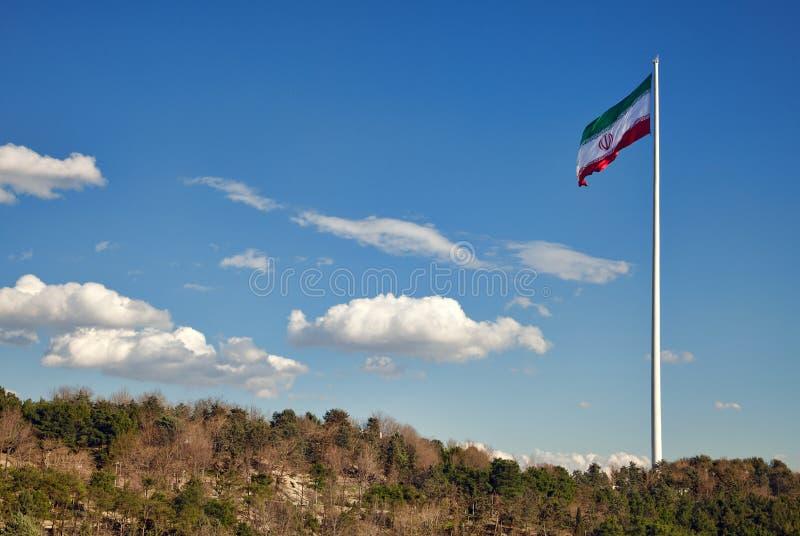 Den stora Iran flaggan som vinkar i vinden mot molnig ovannämnd gräsplan för blå himmel, parkerar område i Teheran royaltyfri bild