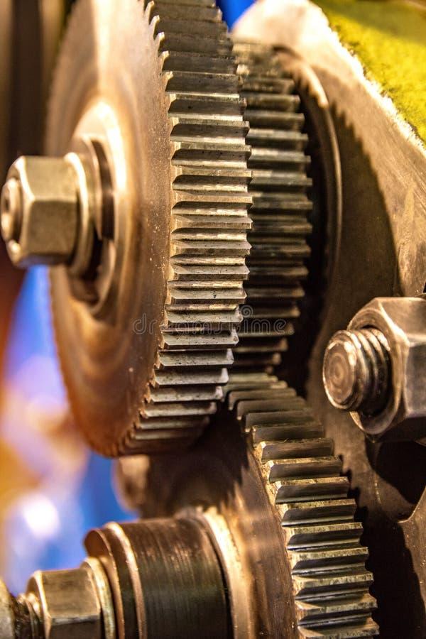 Den stora kuggen rullar in motorkugghjulasken av mekanismen i en fabrik arkivfoton