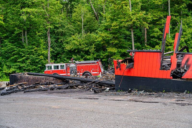 Den stora lastbilen för röd brand nära det utbränt shoppar, släckt brand arkivbild