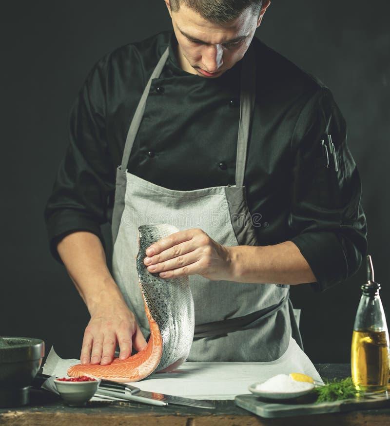 Den stora laxen är i händerna av kockkocken Han använder en kniv för att skiva laxfilén arkivfoton