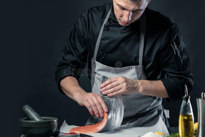 Den stora laxen är i händerna av kockkocken Han använder en kniv för att skiva laxfilén arkivfoto