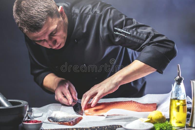 Den stora laxen är i händerna av kockkocken Han använder en kniv för att skiva laxfilén royaltyfri bild