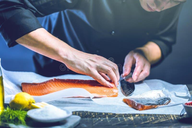 Den stora laxen är i händerna av kockkocken Han använder en kniv för att skiva laxfilén royaltyfria foton