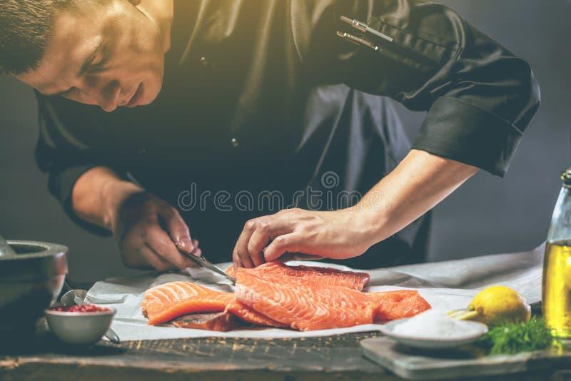 Den stora laxen är i händerna av kockkocken Han använder en kniv för att skiva laxfilén arkivbild