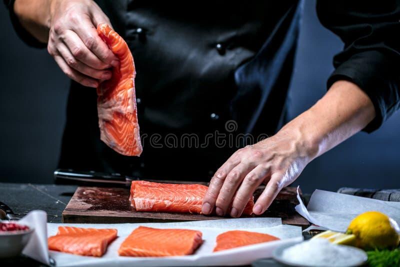 Den stora laxen är i händerna av kockkocken Han använder en kniv för att skiva laxfilén royaltyfria bilder