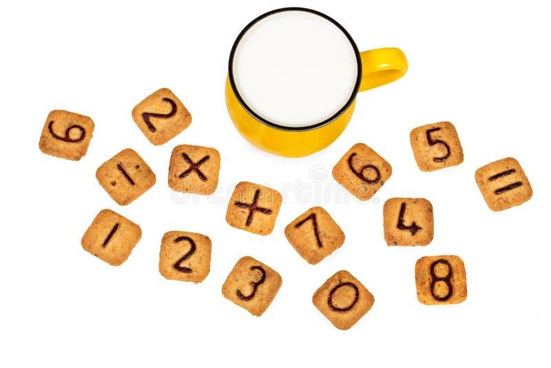 Den stora livliga gula koppen av mjölkar och roliga kakor med nummer som isoleras på vit bakgrund Sund frukost för ett barn royaltyfri fotografi