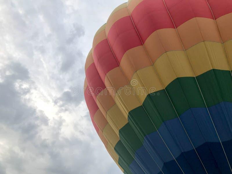 Den stora mång--färgade ljusa runda regnbågen färgade den randiga randiga flygballongen med en korg mot himlen i aftonen arkivfoton