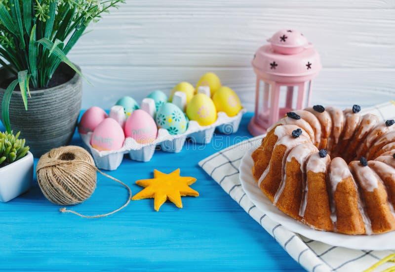 Den stora plattan med kakan och handen målade färgrika ägg, på handduken på blå bakgrund close upp garnering easter royaltyfria bilder