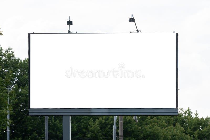 Den stora tomma affischtavlan med himlen som är klar att använda för ny modellannonsering och att marknadsföra gatamassmedia och  royaltyfri fotografi