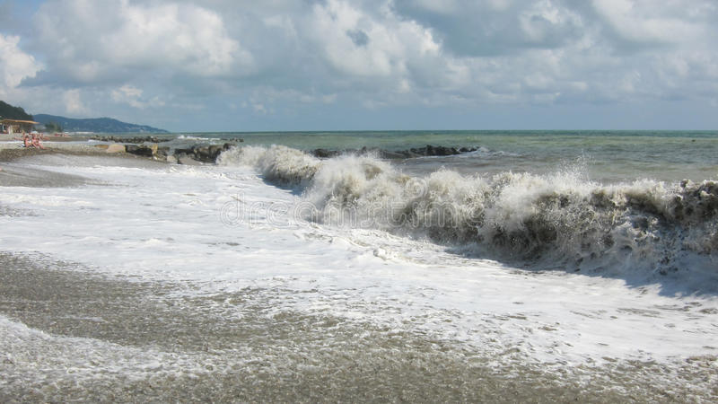 Den stora vågen rullar på den steniga stranden royaltyfri bild