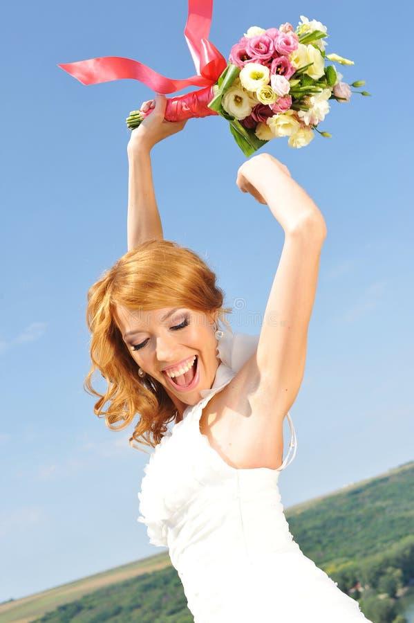 Den strålningsröda haired bruden lyfter buketten i luften royaltyfria bilder