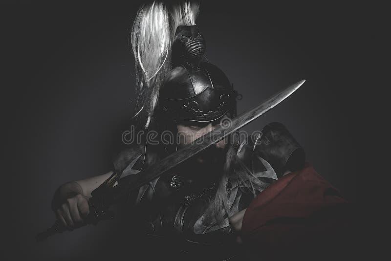 Den Strengh krigarehjälmen, harnesken och röd udde på en slagfält, lurar royaltyfri bild