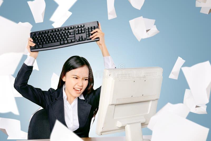 Den stressade asiatiska affärskvinnan med spritt flygpapper önskar att smälla i tangentborddatoren royaltyfri fotografi
