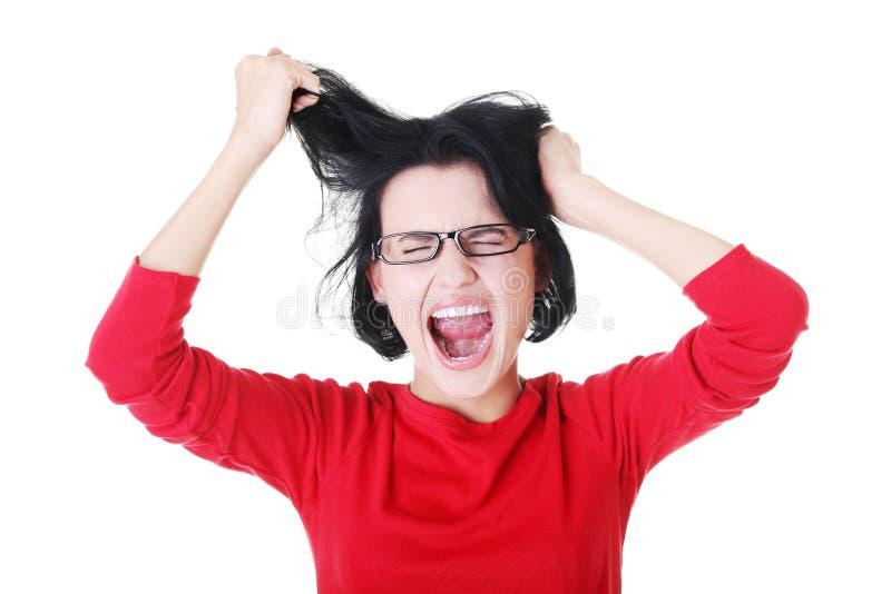 Den stressade kvinnan går galen dra hennes hår. royaltyfria foton
