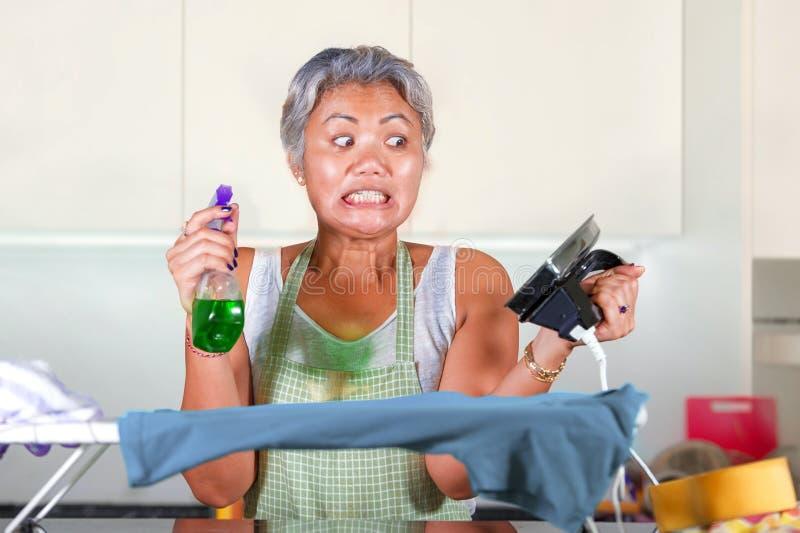 Den stressade mitt ?ldrades den asiatiska kvinnan som stryker i hemmastadd k?kk?nsla f?r sp?nningen som f?rkrossades och tr?ttade arkivbild
