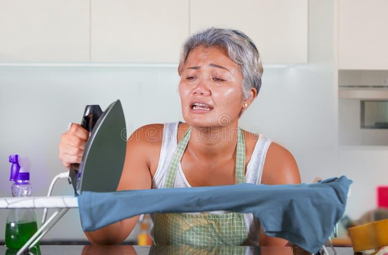 Den stressade mitt ?ldrades den asiatiska kvinnan som stryker i hemmastadd k?kk?nsla f?r sp?nningen som f?rkrossades och tr?ttade arkivfoto