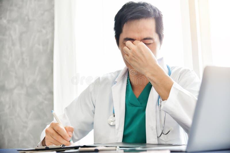 Den stressade unga asiatiska manliga doktorn arbetar arkivfoto