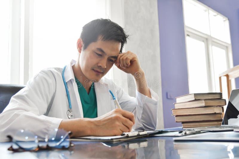 Den stressade unga asiatiska manliga doktorn arbetar royaltyfria bilder