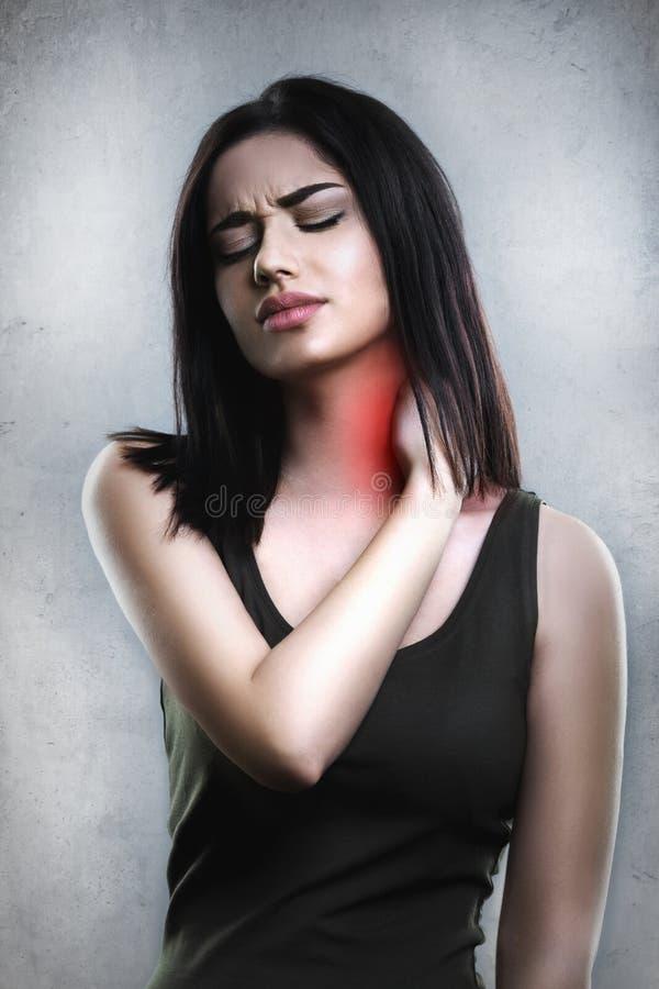 Den stressat unga kvinnan som har en hals, eller tillbaka smärtar royaltyfria bilder