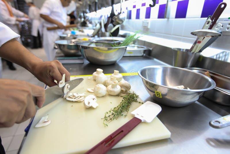 Den suddiga bakgrunden av kocken skivar vita champinjoner på en vit plast- skärbräda i kök arkivbilder