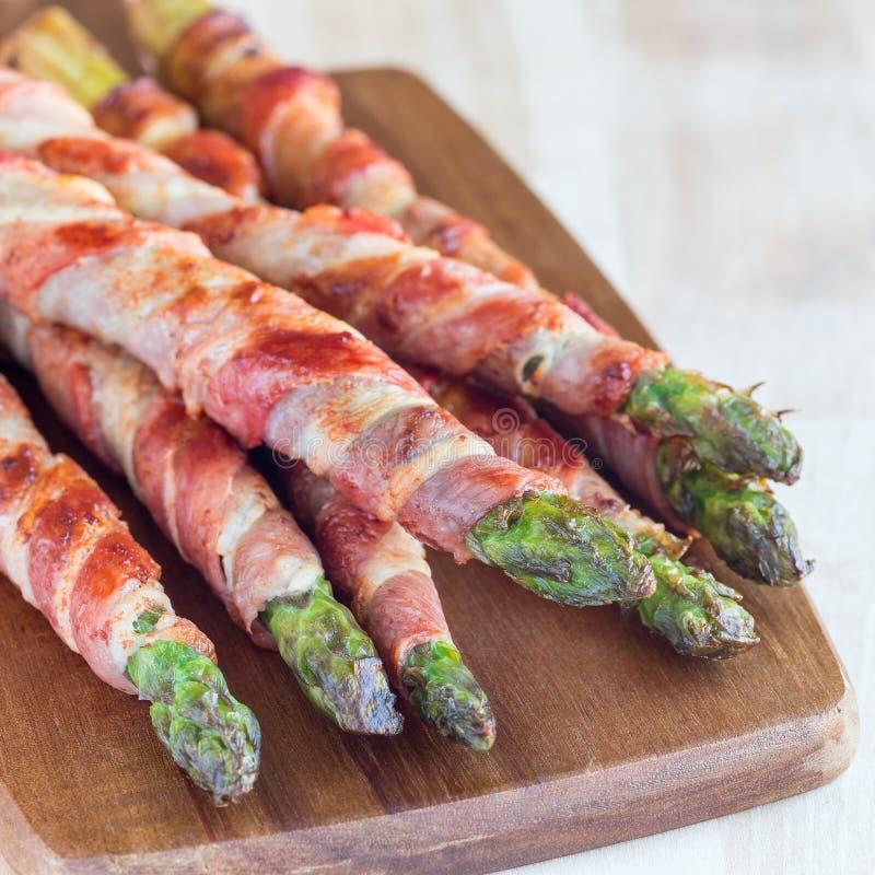 Den sunda aptitretaren, gr?n sparris slogg in med bacon p? tr?br?det, fyrkantigt format arkivbilder