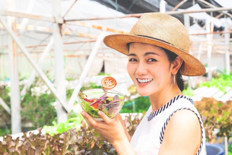 Den sunda asiatiska kvinnan som rymmer salladbunken med tomaten, skivade lycklig livsstil fotografering för bildbyråer