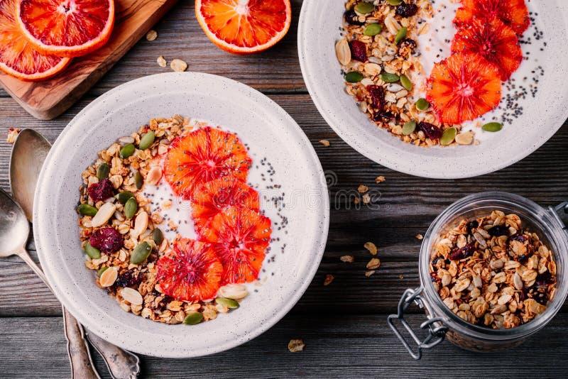 Den sunda frukostbunken av hemlagad granola med nytt yoghurt och blod skivar apelsiner arkivbild