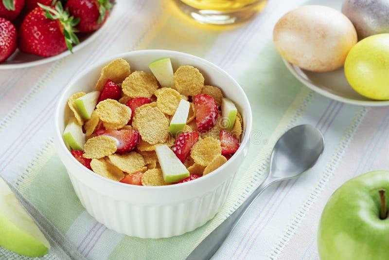 Den sunda frukostcornflakens och jordgubbar med mjölkar och kokade ägg på Easte arkivfoton