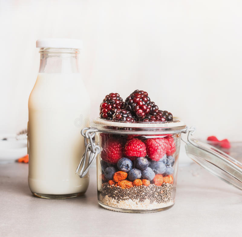 Den sunda frukosten i glass danande med havremjölet, Chia frö, Goji bär, nya bär och flaskan av mjölkar, den främre sikten royaltyfria foton