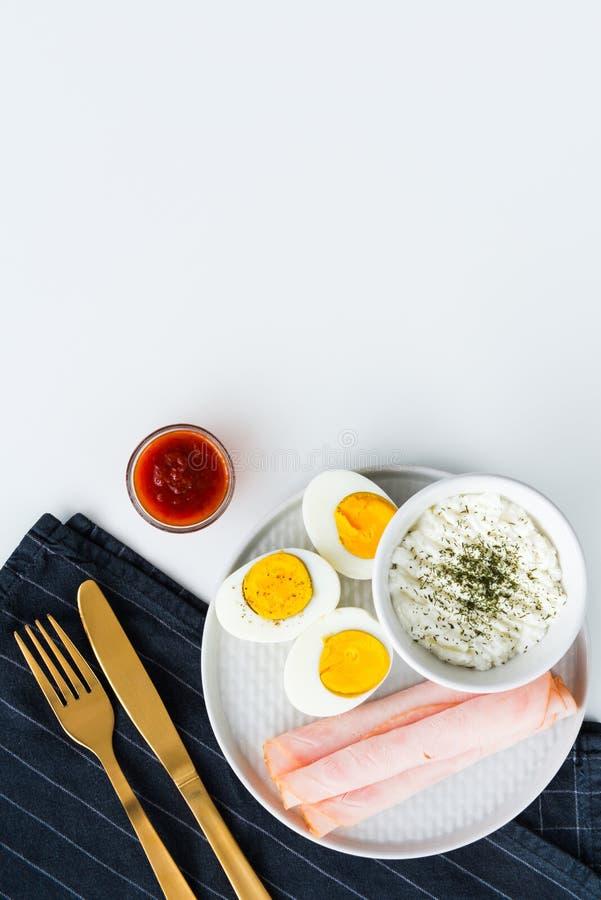 Den sunda frukosten kokade ägg, skinka och ny ost strilad w royaltyfria foton