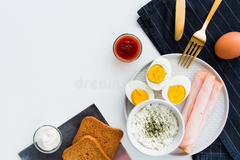 Den sunda frukosten kokade ägg, skinka och ny ost strilad w arkivbild