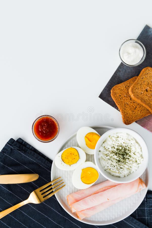 Den sunda frukosten kokade ägg, skinka och ny ost strilad w royaltyfri bild