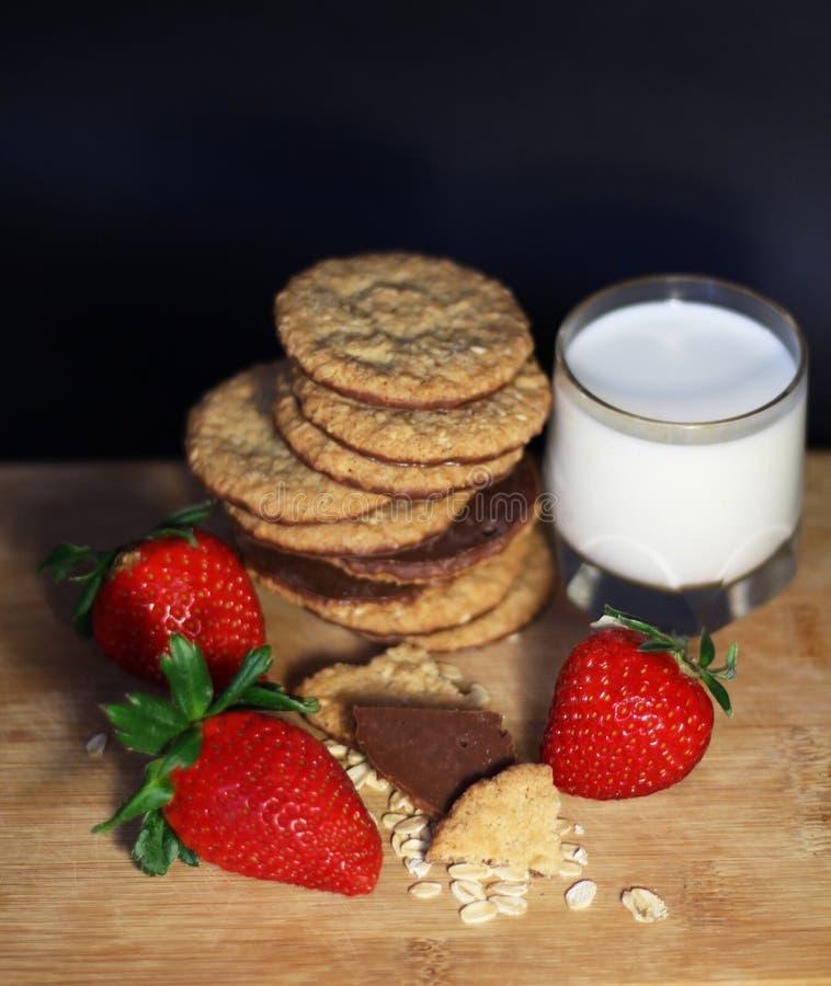 Den sunda frukosten med jordgubben, sädesslag, mjölkar och havrechokladkakor royaltyfri bild