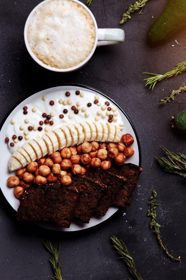 Den sunda frukosten med läckert bröd, bananen, hasselnöten, yoghurten i bunke och en kopp kaffe, latte eller kakao med mjölkar på arkivbilder
