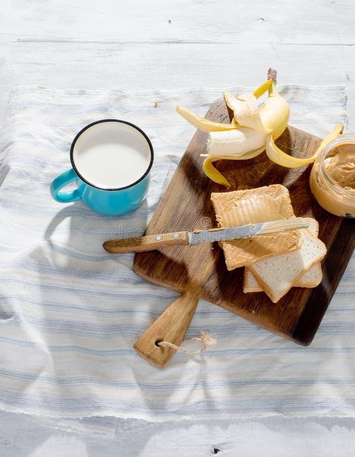 Den sunda frukosten skjuter in jordnötsmör, banan, mjölkar överkant VI royaltyfri bild