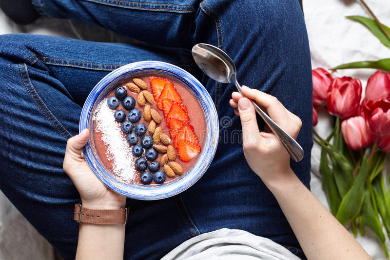 Den sunda frukosten smoothies bowlar i händerna av en kvinna Smoothie från äpplen och bananen, med blåbär, muttrar royaltyfria bilder