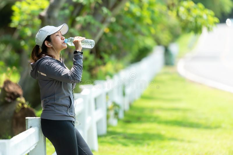 Den sunda idrotts- asiatiska kvinnan dricker rent vatten fr?n flaskan som f?rnyar sig efter ?vning i naturen, parkerar royaltyfria bilder