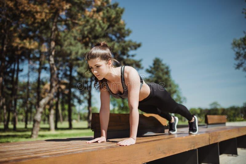 Den sunda idrottsman nenflickan som in sträcker, parkerar på solig dag arkivbilder