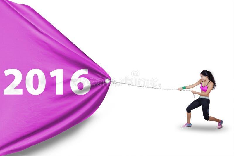 Den sunda kvinnan drar nummer 2016 med flaggan royaltyfri fotografi