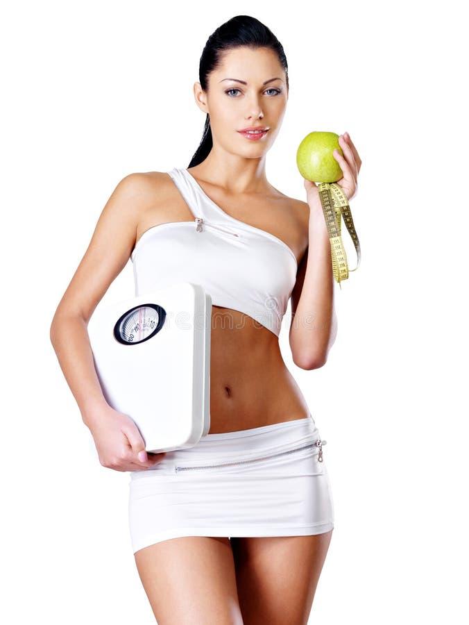 Den sunda kvinnan står med vågen och det gröna äpplet. fotografering för bildbyråer