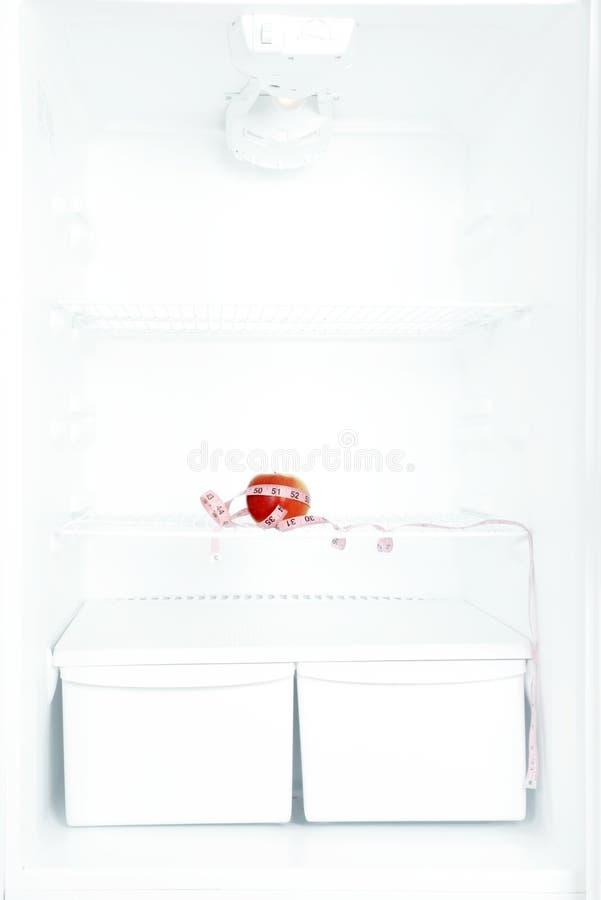 Den sunda livsstilen, bantar begrepp Rött äpple med mätning i tomt kylskåp royaltyfri bild