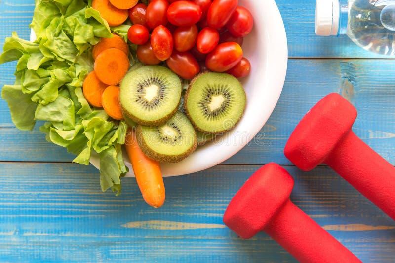 Den sunda livsstilen för kvinnor bantar med sportutrustning, gymnastikskor, den nya grönsaken och flaskan av vatten på trä royaltyfri fotografi
