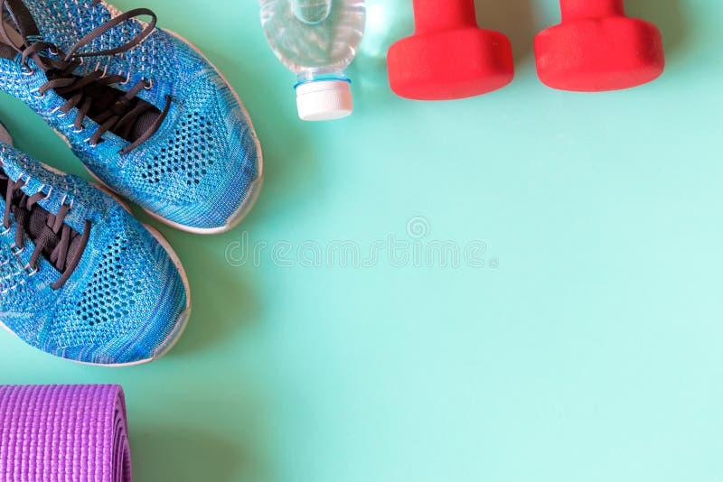Den sunda livsstilen för kvinnor bantar med sportutrustning, gymnastikskor, matt yoga och flaskan av vatten på grön bakgrund arkivbild
