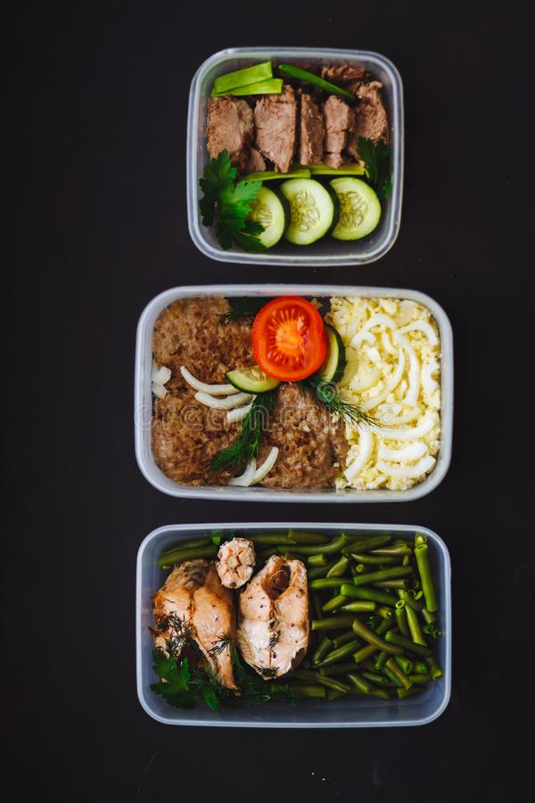 Den sunda maten i behållarna på svart bakgrund: mellanmål matställe, lunch Den bakade fisken, bönor, nötköttkotletter, mosade pot royaltyfri bild