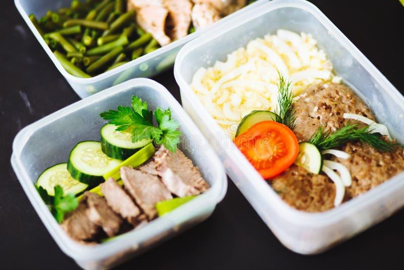 Den sunda maten i behållarna på svart bakgrund: mellanmål matställe, lunch Den bakade fisken, bönor, nötköttkotletter, mosade pot royaltyfri foto