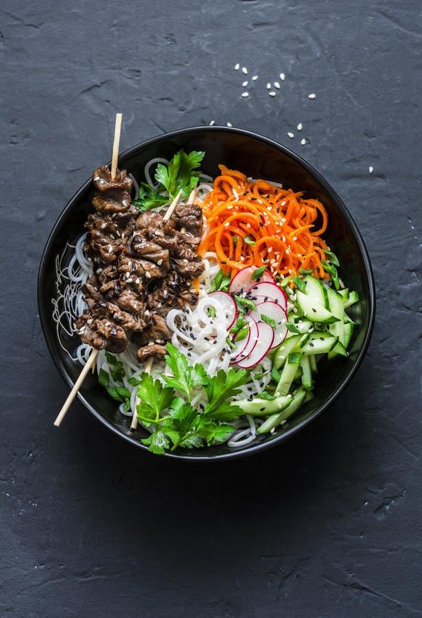 Den sunda matskålen - gnälla steknålar, risnudlar och grönsaksallad på mörk bakgrund arkivbilder