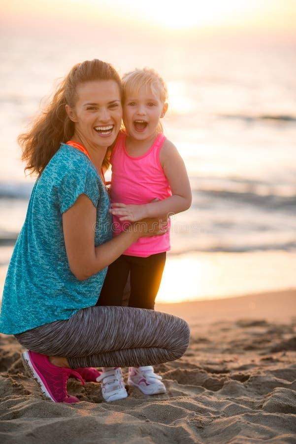 Den sunda modern och behandla som ett barn flickan på stranden arkivbilder