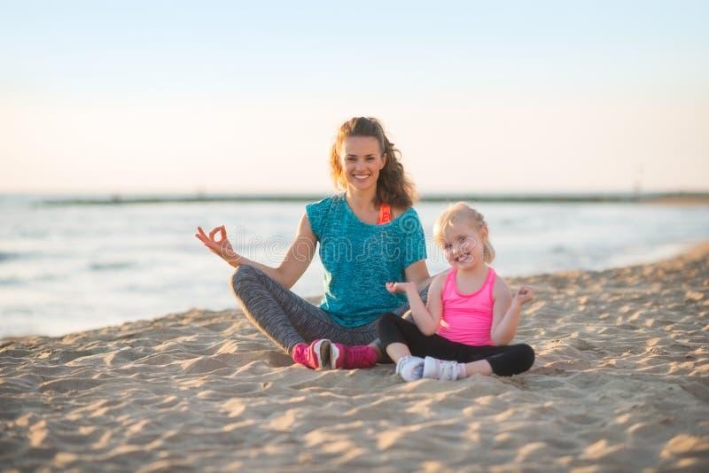 Den sunda modern och behandla som ett barn flickan som gör yoga på stranden arkivbild